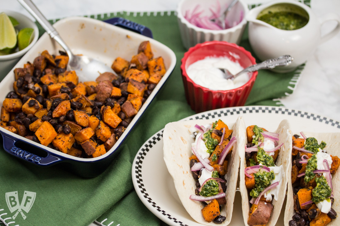Overhead view of prepared ingredients and 3 assembled Roasted Sweet Potato and Black Bean Tacos with Cilantro Chimichurri.