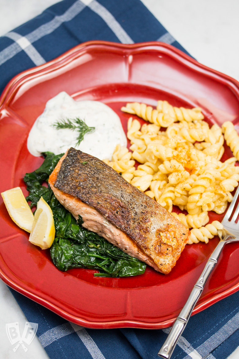 Overhead view of a plate of seared salmon on top of spinach with macaroni and cheese with lemon wedges and sauce in the background.