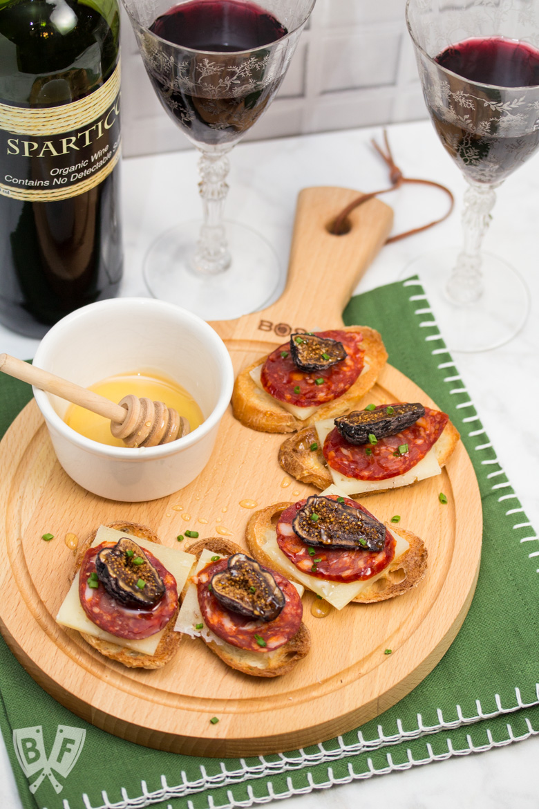 Honeyed Chorizo & Fig Crostini displayed on a board with a honey dipper and a bottle & 2 glasses of Spanish wine.