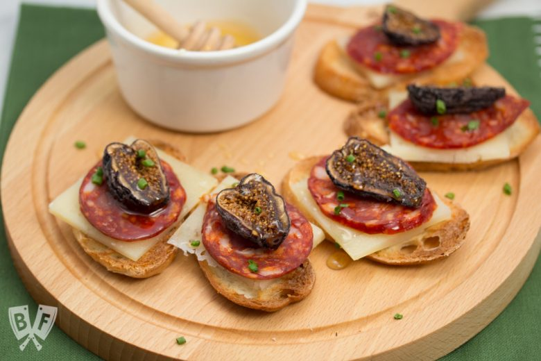 Honeyed Chorizo & Fig Crostini displayed on a board with a honey dipper.