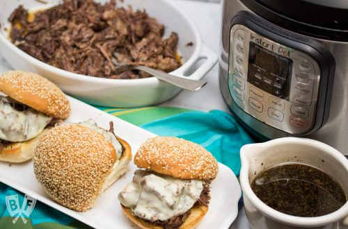 3/4 view of 3 assembled Instant Pot French Dip Sandwiches with au jus, an Instant Pot, and shredded meat alongside.