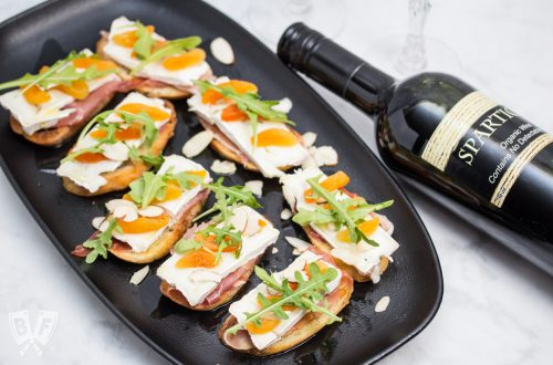 Overhead view of a platter of Prosciutto & Brie Crostini with Dried Apricots next to a bottle of red wine.