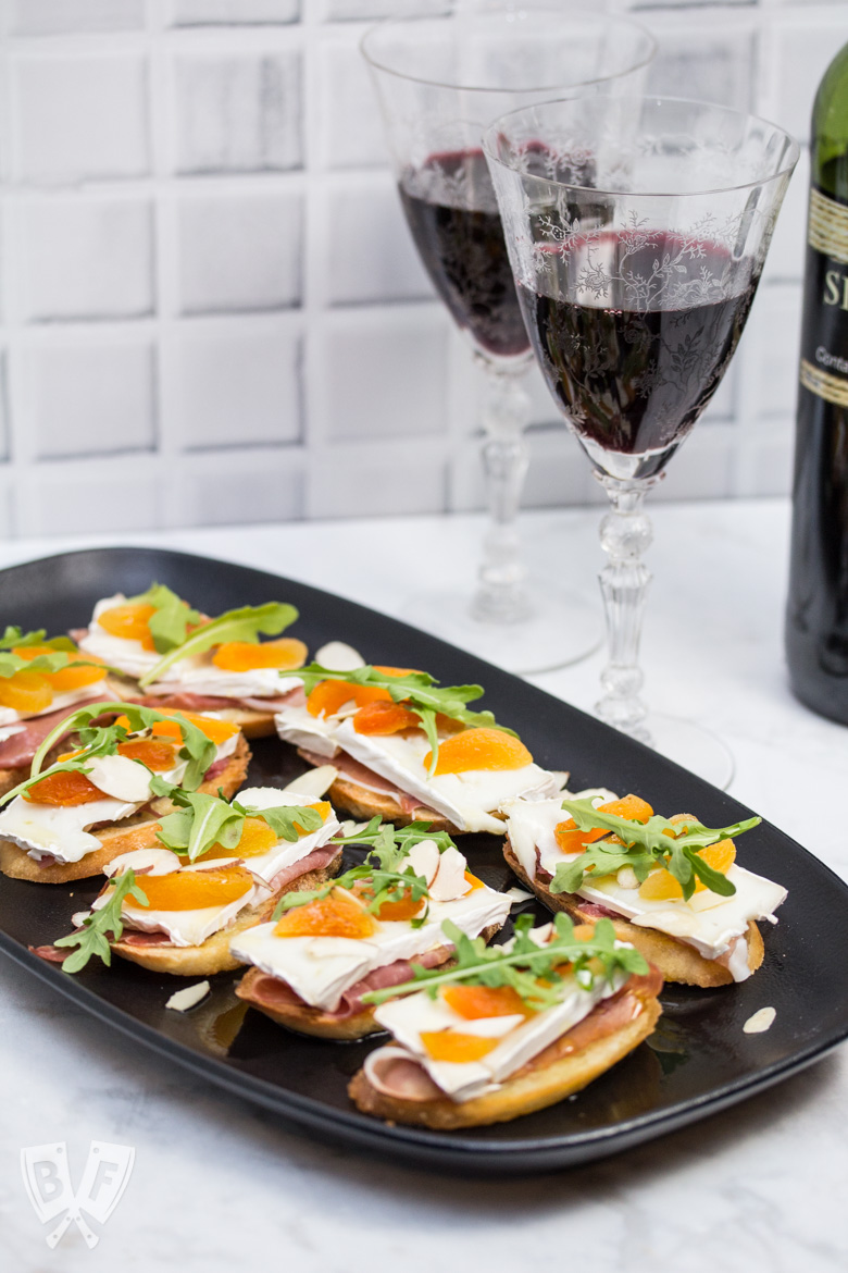 3/4 view of a platter of Prosciutto & Brie Crostini with Dried Apricots next to a bottle of red wine.