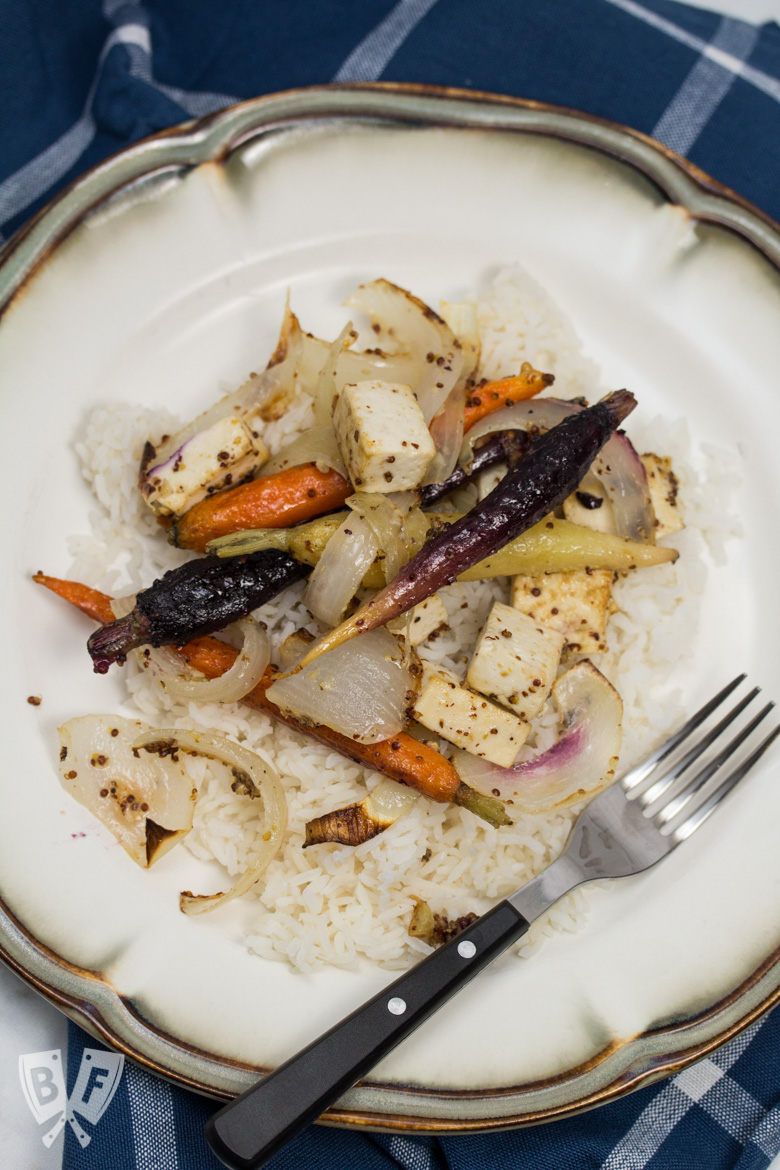 Overhead view of a plate of rice topped with roasted tofu, onions, and rainbow carrots.