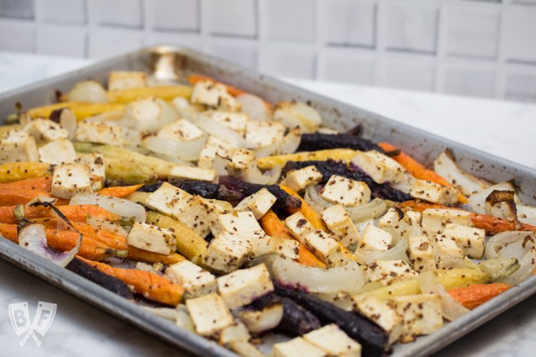 3/4 view of a sheet pan with roasted tofu, onions, and rainbow carrots.