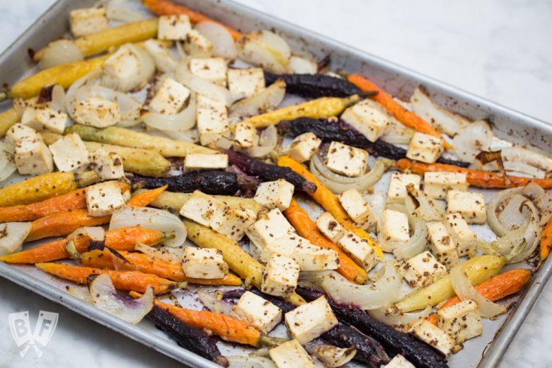 Overhead view of a sheet pan with roasted tofu, onions, and rainbow carrots.