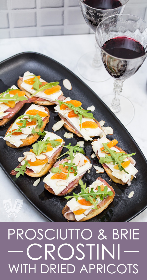 Overhead view of a platter of Prosciutto & Brie Crostini with Dried Apricots next to 2 glasses of red wine.
