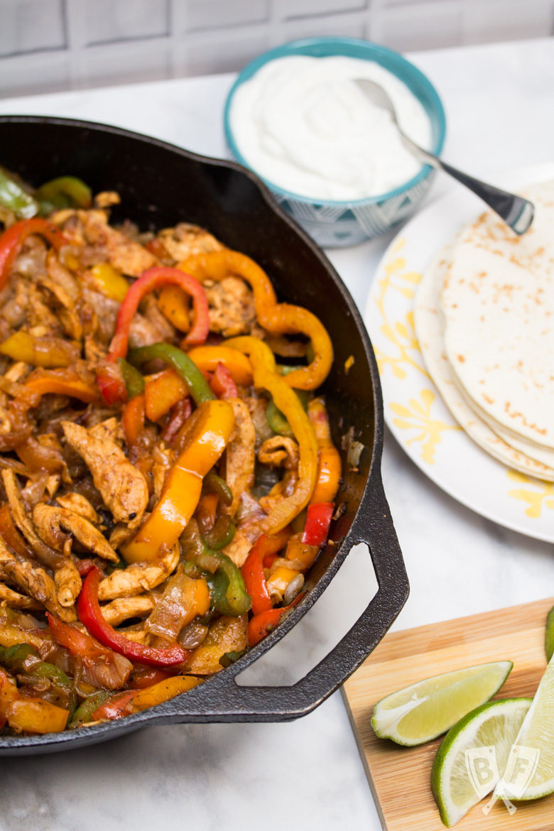 A cast iron skillet filled with chicken fajitas with tortillas and garnishes alongside.
