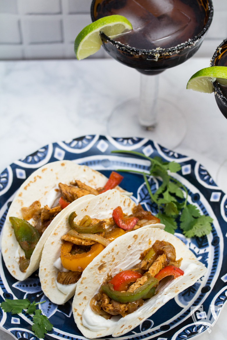 A plate of assembled chicken fajitas with margaritas in the background.