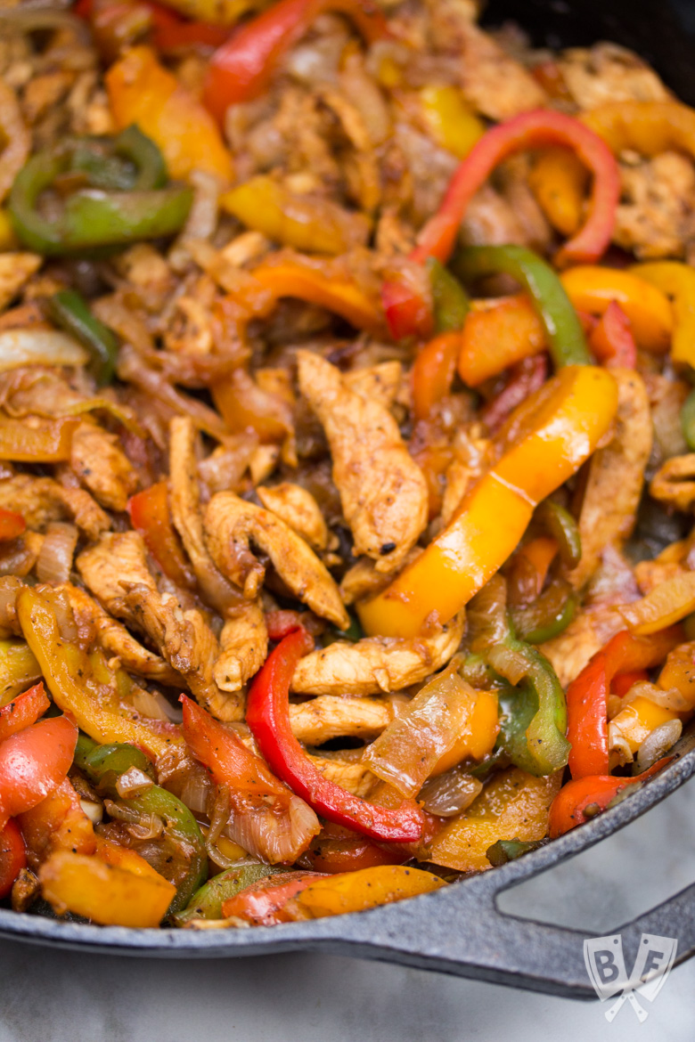 Close up of chicken fajitas in a cast iron skillet.