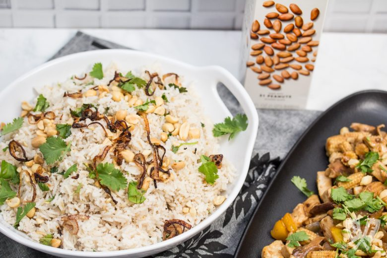 Overhead view of a bowl of Peanutty Rice with Crispy Fried Shallots with a chicken stir-fry to the side and a carton of milked peanuts in the background.
