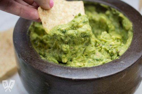 Dipping a chip into freshly made guacamole with margaritas in the background.