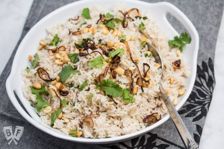 3/4 view of a bowl of Peanutty Rice with Crispy Fried Shallots.