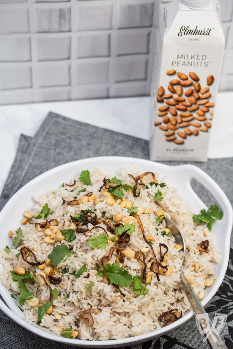 Overhead view of a bowl of Peanutty Rice with Crispy Fried Shallots and a carton of milked peanuts in the background.