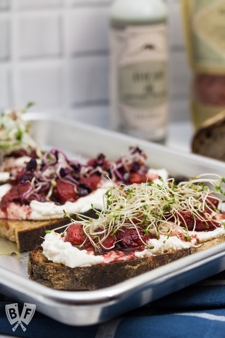 3/4 view of 3 pieces of toast topped with 3 types of sprouts, balsamic-roasted strawberries and ricotta with ingredients in the background.