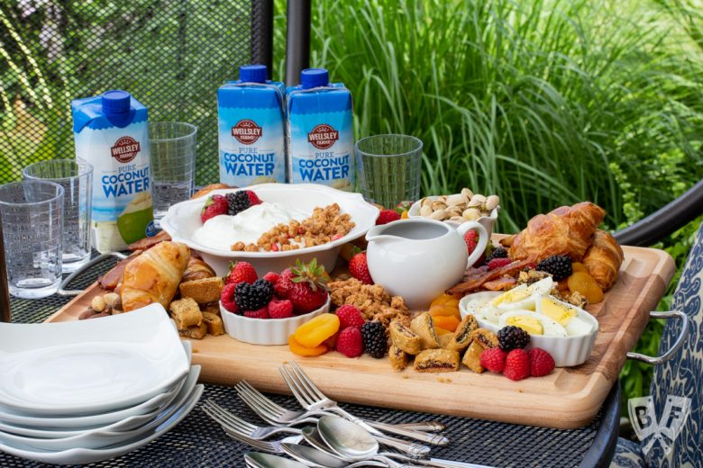 3/4 view of a board of assorted breakfast items sitting on an outdoor table with dishes and beverages around.