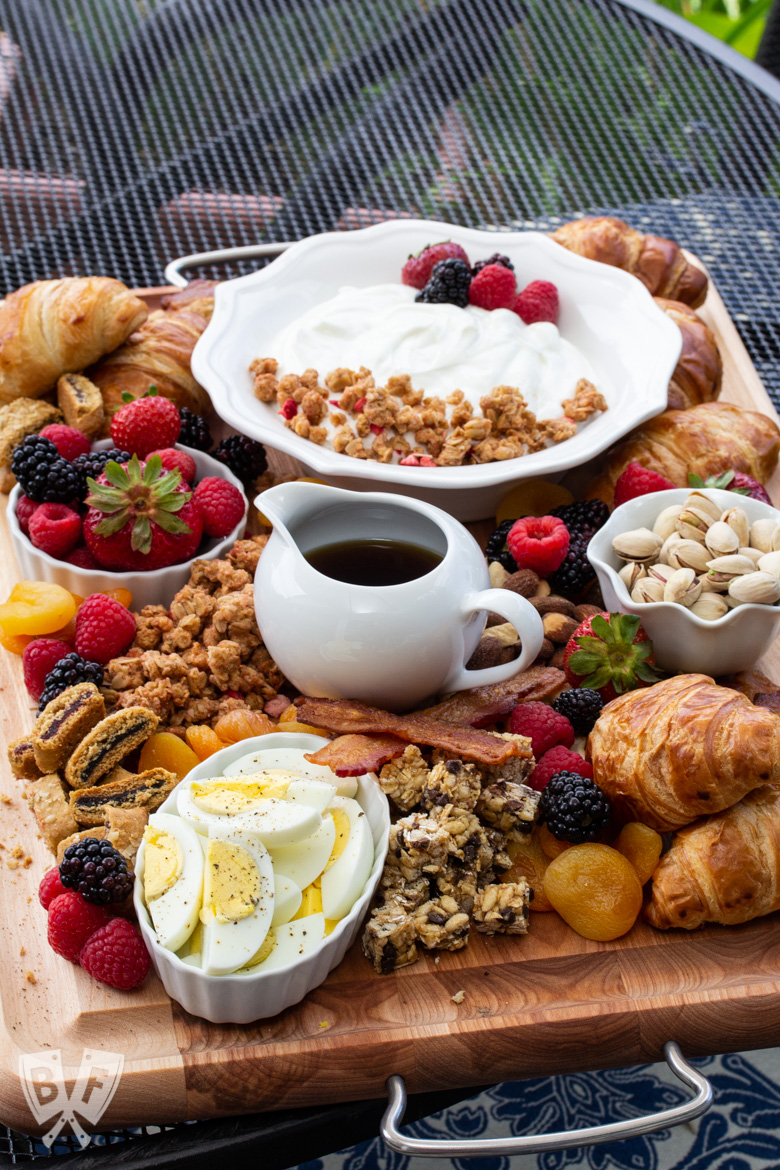 3/4 view of a board of assorted breakfast items sitting on an outdoor table.