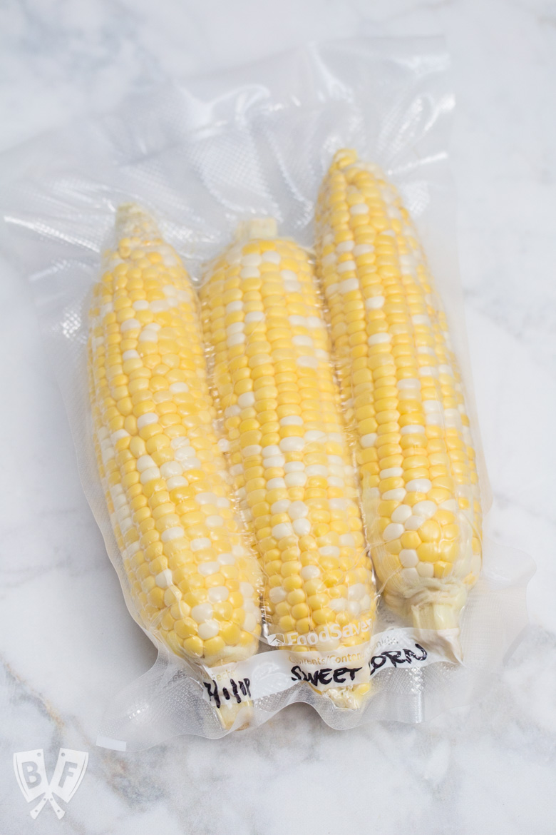 Overhead view of 3 ears of corn in a vacuum-sealed bag.