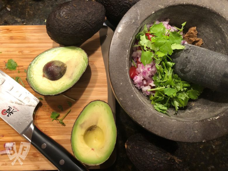 Overhead view of the ingredients for freshly made guacamole with a mortar and pestle.