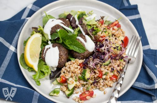 Overhead view of a plate of Mediterranean Farro Salad with Spiced Beef Patties drizzled with yogurt over greens served with lemon wedges and fresh herbs.