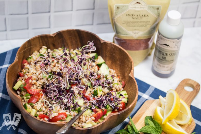 Overhead view of Mediterranean Farro Salad, with ingredients in the background and a cutting board of lemon wedges with fresh herbs.