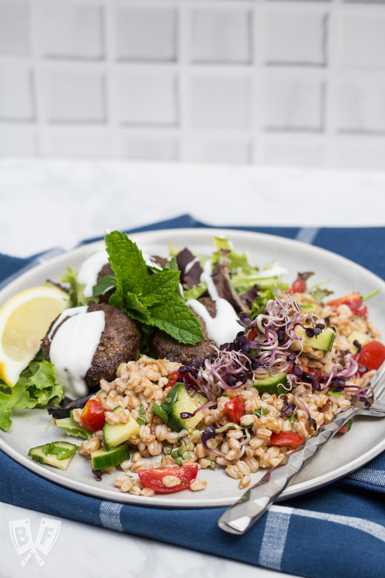 3/4 view of a plate of Mediterranean Farro Salad with Spiced Beef Patties drizzled with yogurt over greens served with lemon wedges and fresh herbs.