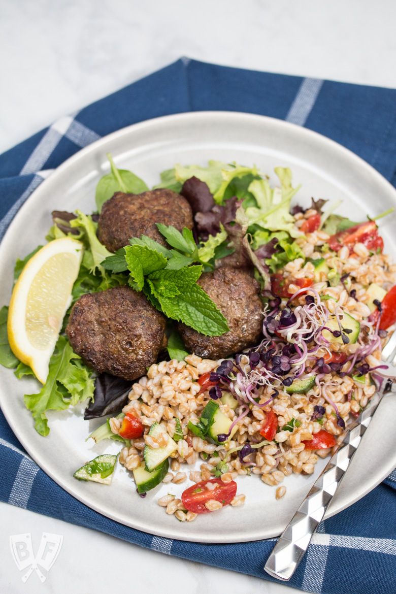 Overhead view of a plate of Mediterranean Farro Salad with Spiced Beef Patties over greens served with lemon wedges and fresh herbs.