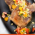 Overhead view of a platter of pork chops with a corn and tomato salad.