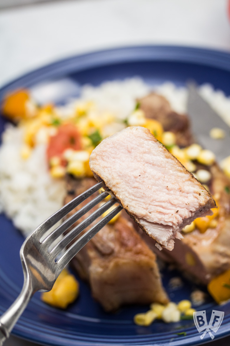 Close up of a cut piece of pork chop served with rice with a corn and tomato salad.