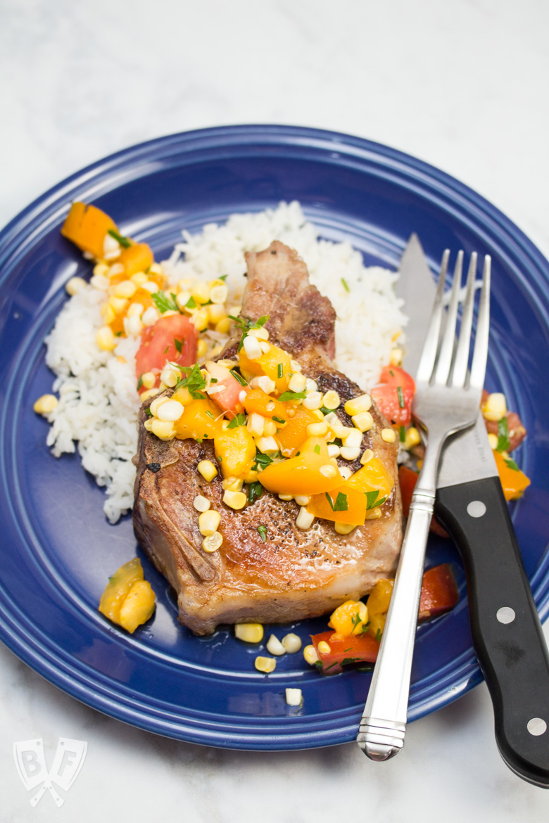 Overhead view of a pork chop over rice with a corn and tomato salad.