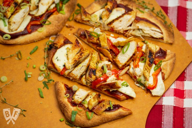 Overhead view of sliced BBQ Chicken Pizza with Smoked Mozzarella on a pizza peel.