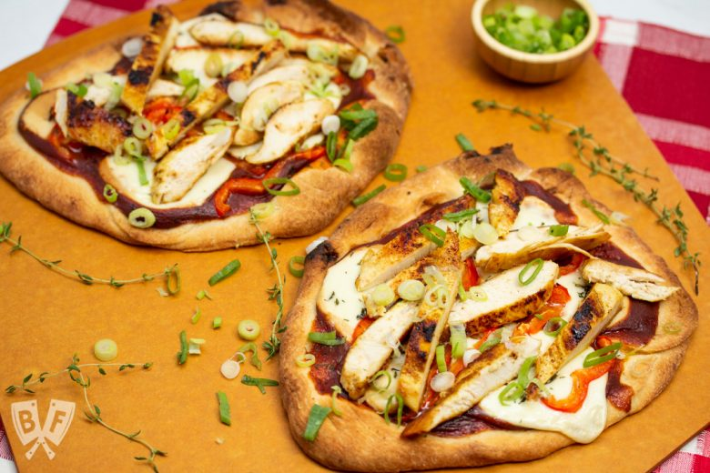 Overhead view of BBQ Chicken Pizza with Smoked Mozzarella on a pizza peel.
