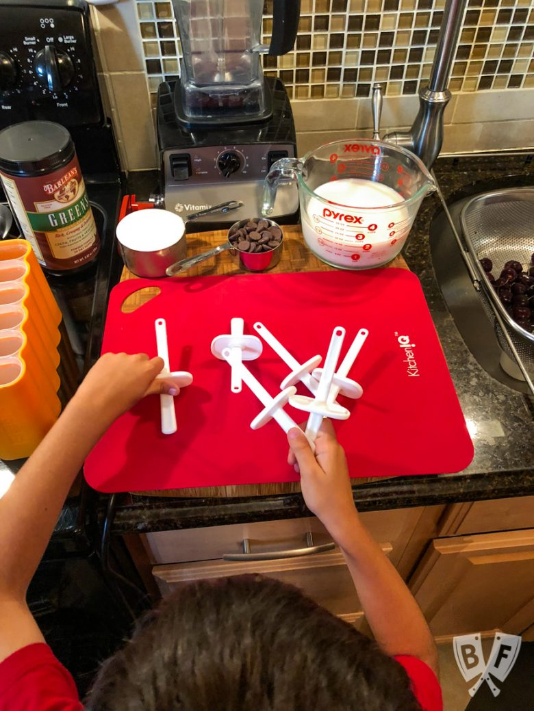 Overhead view of a child assembling popsicle holders with ingredients and equipment needed to make Black Forest Popsicles