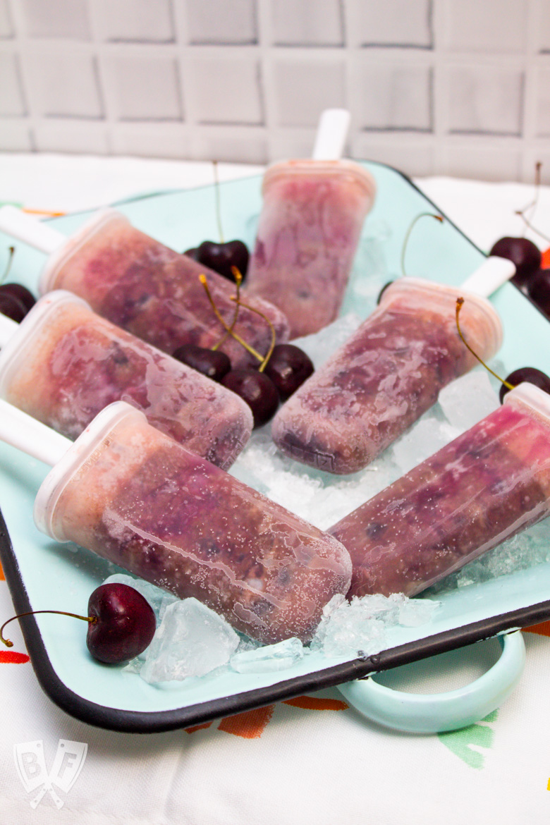 Overhead view of a tray of ice with Black Forest Popsicles and fresh cherries.