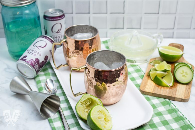 3/4 view of ingredients and copper mugs for making Cucumber Moscow Mule Cocktails.