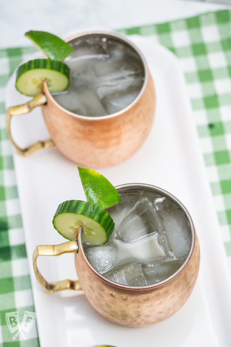 Overhead view of 2 copper mugs filled with a Cucumber Moscow Mule cocktails with ingredients alongside.