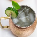 Overhead view of a copper mug filled with a Cucumber Moscow Mule cocktail with ingredients alongside.