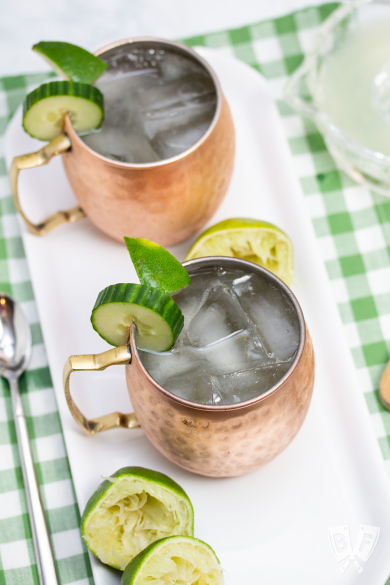 Overhead view of 2 copper mugs filled with Cucumber Moscow Mule cocktails with ingredients alongside.