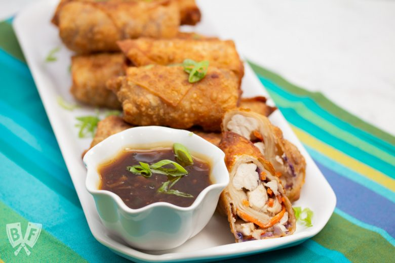 3/4 view of a platter of General Tsao's Chicken Egg Rolls with a bowl of dipping sauce.