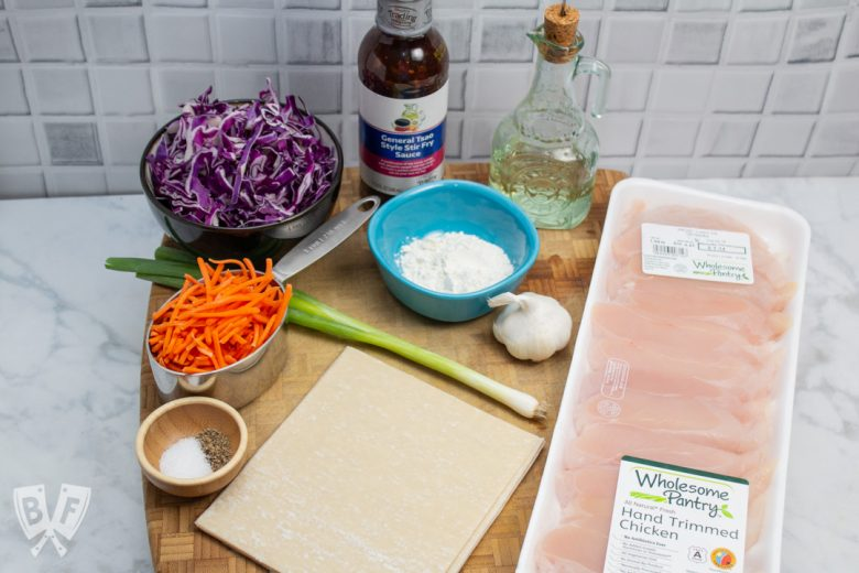 3/4 view of a cutting board with the ingredients for General Tsao's Chicken Egg Rolls.