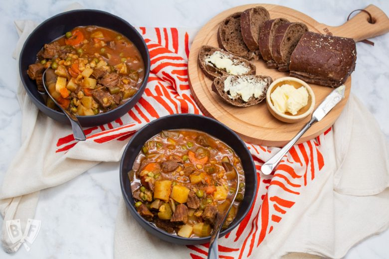 Overhead view of 2 bowls of beef stew with bread and butter.