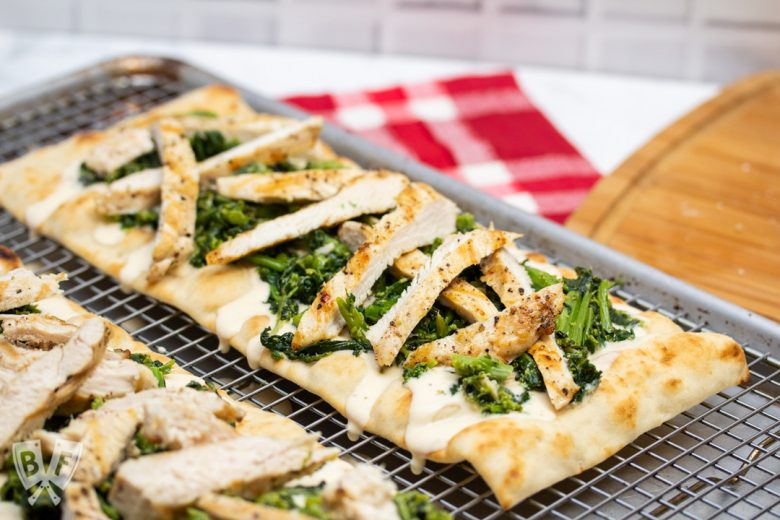 2 chicken and broccoli rabe pizzas sitting on a metal baking rack.