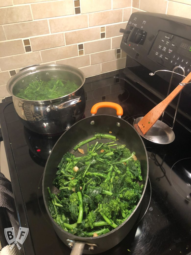 Broccoli rabe on a cutting board with a skillet of garlic and a pot of boiling water in the background.