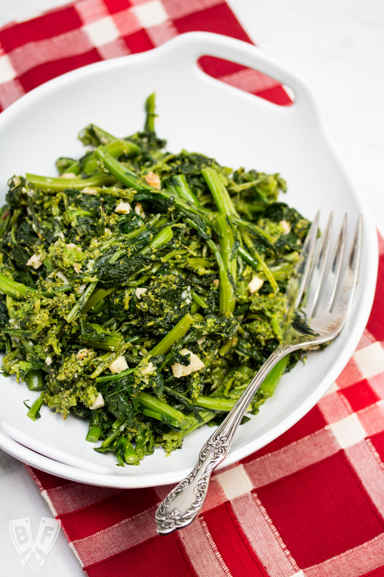 Overhead view of a bowl of broccoli rabe and garlic with a serving fork.