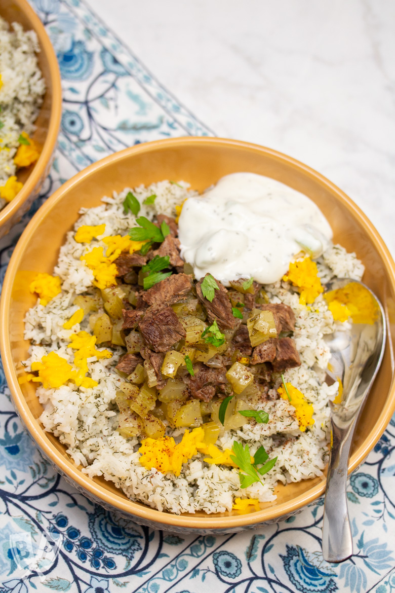Overhead view of a bowl of Instant Pot Persian Beef and Celery Stew (Khoreshe Karafs) with mast-o-khiar over dill rice.