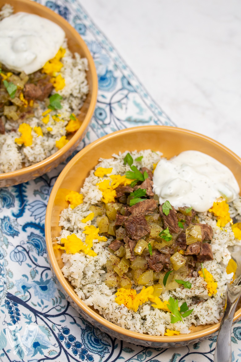 Overhead view of 2 bowls of Instant Pot Persian Beef and Celery Stew (Khoreshe Karafs) with mast-o-khiar over dill rice.