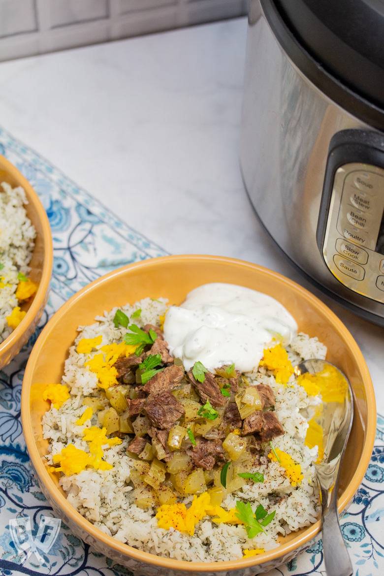 Overhead view of 2 bowls of Instant Pot Persian Beef and Celery Stew (Khoreshe Karafs) with mast-o-khiar over dill rice next to an Instant Pot.