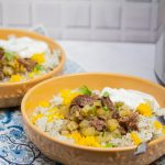 3/4 view of 2 bowls of Instant Pot Persian Beef and Celery Stew (Khoreshe Karafs) with mast-o-khiar over dill rice next to an Instant Pot.