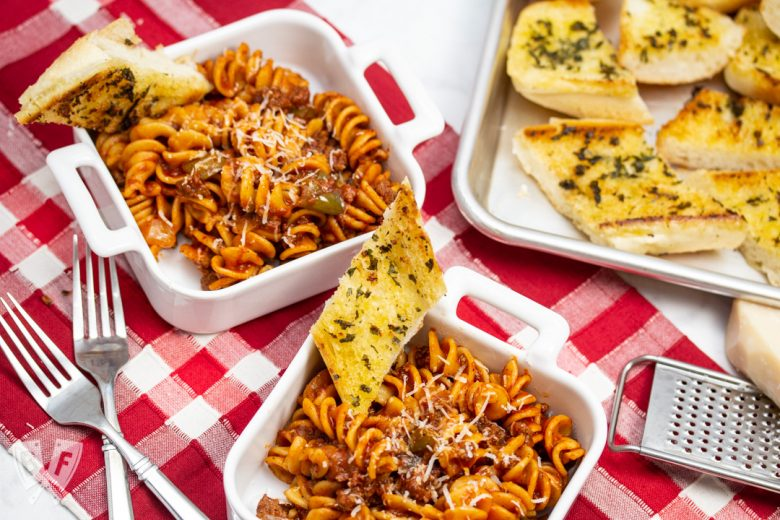 Overhead view of dishes of Instant Pot Tomato Beef Pasta with serving dishes with Parmesan cheese and a tray of garlic bread in the background.
