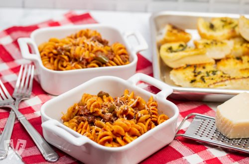 3/4 view of dishes of Instant Pot Tomato Beef Pasta with serving dishes with Parmesan cheese and a tray of garlic bread in the background.